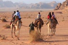 Tourists riding camels at sunset in the Wadi Rum desert, Jordan Stock Photos