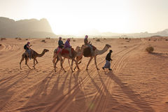 Tourists riding camels at sunset in the Wadi Rum desert, Jordan Stock Photo