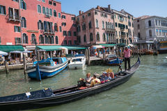 Tourists riding on gondola along the Grand Canal in Venice, Italy. Stock Photo