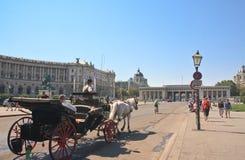 Tourists riding horse-drawn carriage. Hofburg in Vienna, Austria Stock Image