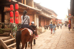 Tourists riding a horse in Shuhe ancient town. Stock Photo