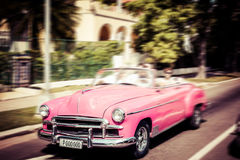 Tourists riding in oldtimer car in Havana. Concept of Cuba attra. Ctions. Shallow DOF, filter applied. Toned, horizontal Royalty Free Stock Photography