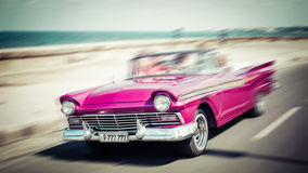 Tourists riding in oldtimer car in Havana. Concept of Cuba attra. Ctions. Shallow DOF, filter applied. Toned, horizontal Stock Photos