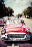 Tourists riding in oldtimer car in Havana. Concept of Cuba attra. Ctions. Shallow DOF, filter applied. Toned, horizontal Royalty Free Stock Photo