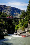 Tourists Riding Shotover Jet Boat at Queenstown, New Zealand. QUEENSTOWN, NZ - OCTOBER 22, 2016: Tourists enjoy a high speed jet boat ride on the Shotover River Stock Photography