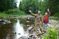 Tourists by river. Cheerful hikers waving hands while standing on stones by forest river Stock Image