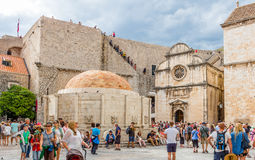 Tourists roaming around Church of Saint Saviour and Onofrio`s Fo. DUBROVNIK, CROATIA - JULY 16th, 2016: tourists roaming Stradun street starting square in Old Royalty Free Stock Images