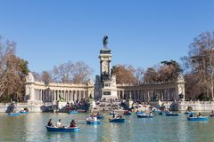 Tourists rowing traditional blue boats on lake in Retiro city park on a nice sunny winter day in Madrid, Spain. royalty free stock photos