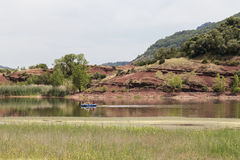 Tourists on Rubber Boat on Lake Salagou with Red Rocks, France Royalty Free Stock Image
