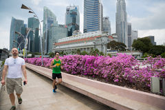 Tourists and runner on the Esplanade Drive in Singapore Royalty Free Stock Image