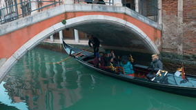 Tourists Sailing in Gondola along the Water Canal. VENICE, ITALY - FEBRUARY 16, 2015: Traditional Venetian gondola boat is sailing under the bridge over the stock video footage