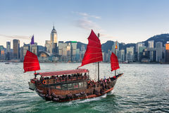Tourists on sailing ship with red sails crosses Victoria harbor Royalty Free Stock Photos