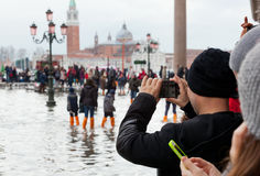 Tourists in San Marco square with high tide, Venice, Italy. Royalty Free Stock Photo