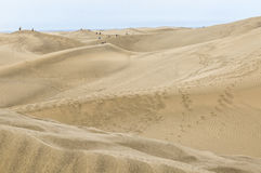 Tourists and sand dunes at Maspalomas on Gran Canaria. Royalty Free Stock Photo