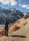Tourists shoot black mountain with snow on the top and yellow stone ground at Thangu and Chopta valley in winter in Lachen. Royalty Free Stock Photography