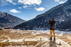 Tourists shoot black mountain with snow on the top and yellow stone ground at Thangu and Chopta valley in winter in Lachen. Royalty Free Stock Image
