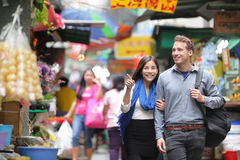 Tourists shopping in street market in Hong Kong. Couple walking looking around at small shops. Asian woman, Caucasian man Royalty Free Stock Photos
