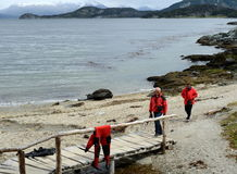 Tourists on the shore of the Beagle channel in the national Park of Tierra del Fuego. Royalty Free Stock Images