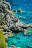 Tourists shorkling between Rocks in Azure Bay of Beautiful Paleokastritsa in Corfu Island, Greece. Vertical orientation Stock Photos