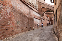 Tourists in Sibiu walking near a brick wall Stock Photos