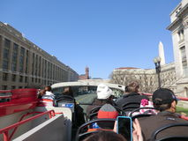 Tourists sight-seeing on Hop-on Hop-off Bus, Washington DC, USA. Top of Washington Monument can be seen at distance Royalty Free Stock Image
