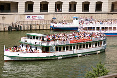 Tourists On Sightseeing Boats Travel Chicago River. CHICAGO, IL - MAY 27:  Several sightseeing boats loaded with tourists travel down the Chicago River.  Chicago Royalty Free Stock Image