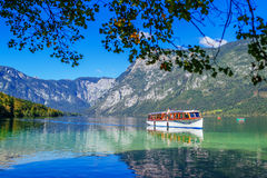 Tourists sightseeing Bohinj lake and surrounding from boat Stock Photos