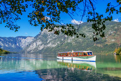 Tourists sightseeing Bohinj lake and surrounding from boat Stock Photo