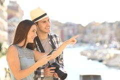 Tourists sightseeing in a coast town. Couple of happy tourists sightseeing in a coast town street royalty free stock photography