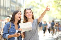 Tourists sightseeing holding a map and pointing up. Two happy tourists sightseeing holding a map and pointing up in the street Royalty Free Stock Photo