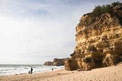 Tourists sightseeing sea caves on wonderful sandy beach with huge cliffs and rocks. Admiring wonderful sandy beach with huge cliffs and rocks of praia da marinha Royalty Free Stock Photos