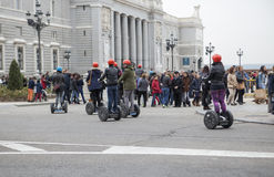 Tourists sightseeing on segway tour of Madrid, Royal Palace, Spa Royalty Free Stock Photography
