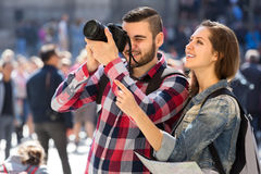 Tourists sightseeing and taking photos. Couple of happy tourists with a map wearing backpacks sightseeing and taking photographs Stock Images