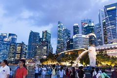 Tourists at the Singapore Merlion Park and Night Cityscape photo. Of Central Business District, Singapore, April 14 2018 Stock Photo