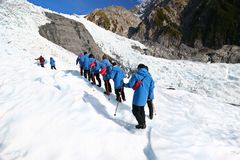 Tourists in single file ascending icy slope at glacier exploration. Heli hike guided tour on Franz Josef Glacier, New Zealand royalty free stock photography