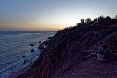 Tourists OverLook The Pacific Ocean in Malibu. Tourists sit on a cliff overlooking the Pacific Ocean in Malibu, California Stock Images