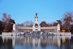 Tourists sit near monument to Alfonso XII at pond in Retiro Park Stock Images