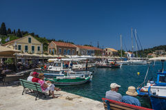 Tourists sit and relax amongst the restaurant, taverners and yac. FISKARDO PORT, KEFALONIA ISLAND, GREECE - 8 MAY: Tourists sit and relax amongst the restaurant Royalty Free Stock Photo