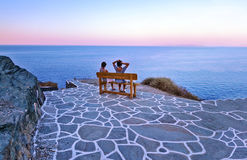 Tourists sitting on bench at Sifnos castle Cyclades Greece Stock Image
