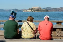 Tourists sitting on a bench with views of the island and Alcatraz prison in the background from Pier 39 in San Francisco stock images