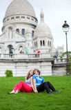 Tourists sitting on the grass by Sacre-Coeur Stock Images