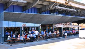 Tourists sitting and relaxing at a street restaurant on the Pier facing Hudson river in Lower Manhattan, New York. stock images