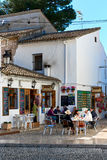 Tourists sitting in a sidewalk cafe in the Guadalest village Royalty Free Stock Photos