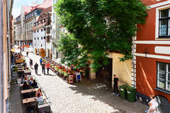 Tourists sitting in a sidewalk cafe in the old town of Riga royalty free stock images
