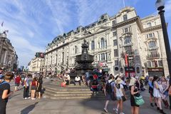Tourists sitting on the steps of the Shaftesbury Memorial Fountain, Piccadilly Circus, London, United Kingdom Stock Image