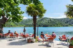 Tourists sitting at a waterside cafe Royalty Free Stock Images