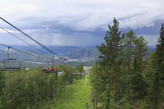 Tourists at the ski lift on a background of thunderclouds Stock Image