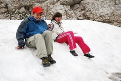 Tourists sliding on snowfield. Royalty Free Stock Photography