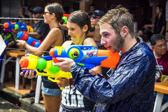 Tourists at Songkran Festival in Bangkok, Thailand. Caucasian tourists shooting water guns at Songkran festival, the traditional Thai New Year, on Khao San Road stock images