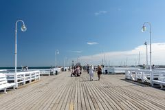 Tourists on Sopot Pier. Sopot, Poland - July 27, 2018: Tourists walking on wooden Sopot Pier in a sunny day. It is the longest wooden pier in Europe and is stock images